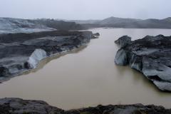 En grumset flod, der flyder under isen